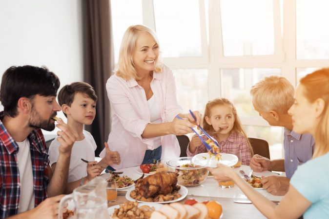 A mom serves her family a meal as they happily eat it