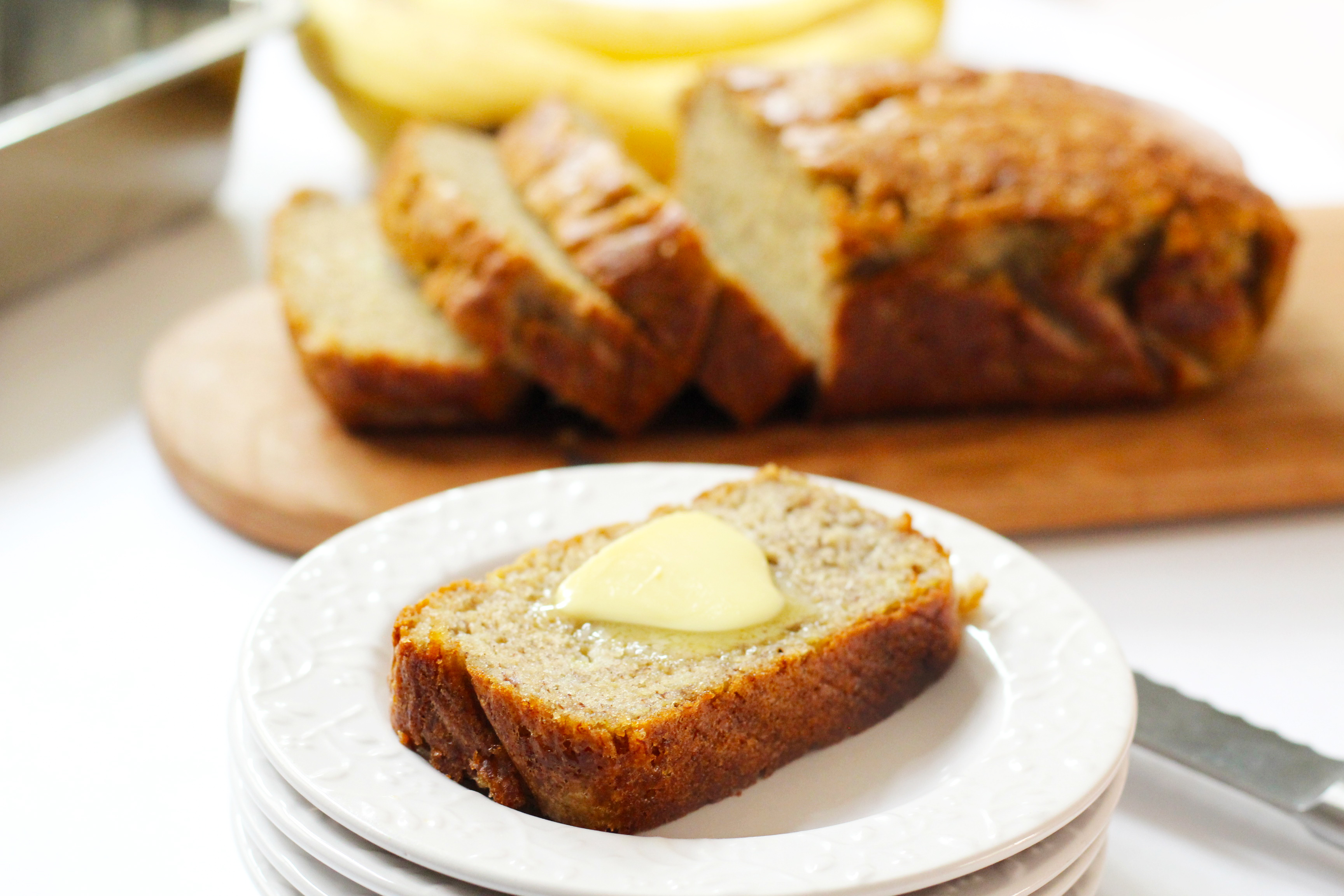 Classic Banana Bread sliced and topped with butter